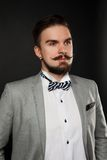 Handsome guy with beard and mustache in suit. On dark background in studio Royalty Free Stock Images
