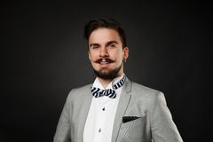 Handsome guy with beard and mustache in suit. On dark background in studio Royalty Free Stock Image