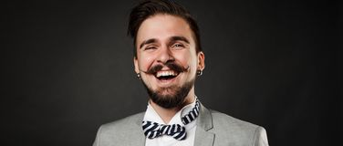 Handsome guy with beard and mustache in suit. On dark background in studio Stock Photos