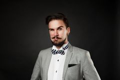Handsome guy with beard and mustache in suit. On dark background in studio Royalty Free Stock Photos