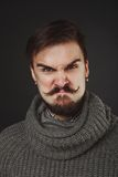 Handsome guy with beard in wool pullover. Handsome guy with beard and mustache in wool pullover on dark background in studio Royalty Free Stock Photos