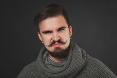 Handsome guy with beard in wool pullover. Handsome guy with beard and mustache in wool pullover on dark background in studio Stock Photos