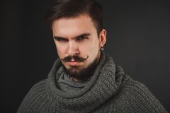 Handsome guy with beard in wool pullover. Handsome guy with beard and mustache in wool pullover on dark background in studio Stock Image