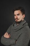 Handsome guy with beard in wool pullover. Handsome guy with beard and mustache in wool pullover on dark background in studio Royalty Free Stock Images