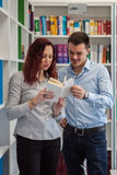 Handsome guy and beautiful redhead girl studying in the library royalty free stock photos