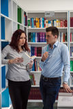 Handsome guy and beautiful redhead girl studying in the library Royalty Free Stock Image