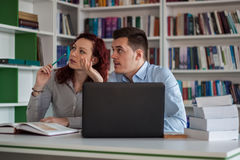 Handsome guy and beautiful redhead girl studying in the library Royalty Free Stock Photo