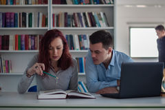 Handsome guy and beautiful redhead girl studying in the library Stock Images