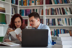 Handsome guy and beautiful redhead girl studying in the library Royalty Free Stock Photography