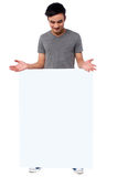 Handsome guy behind blank ad board Royalty Free Stock Photo