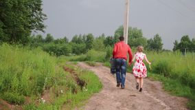 Handsome guy and blonde girl walking on the grass near forest. Clip. Couple fleeing in the forest.  stock video footage