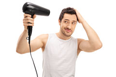 Handsome guy blow drying his hair. Isolated on white background Royalty Free Stock Photo