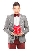 A handsome guy with bow tie holding a gift Royalty Free Stock Images