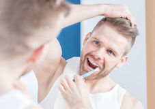 Handsome guy brushing his teeth Royalty Free Stock Photos