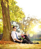 Handsome guy with a bunch of flowers in a park relaxing on a sun Stock Photos