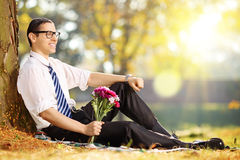 Handsome guy with a bunch of flowers in park relaxing Stock Photo
