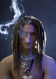 A handsome guy with a cigarette and a variety of stylish silver. A young stylish man with dreadlocks and a lot of silver jewelry smoking a cigarette, blue filter Royalty Free Stock Image