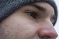 Handsome guy close-up. Part of the body of the eyes. Green eyes. Macro shooting. A gray hat. Winter Royalty Free Stock Image