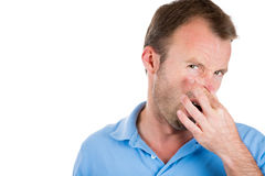 Handsome guy closing nose because something stinks, Stock Image