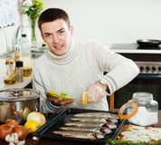 Handsome guy cooking raw fish with lemon Stock Photos