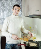 Handsome guy cooking  steak of porbeagle in frying pan Royalty Free Stock Photos