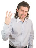Handsome guy counts on his fingers three isolated. Young smiling dark haired caucasian man in light blue striped shirt counting on fingers three isolated on Stock Photography