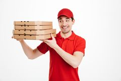 Handsome guy from delivery service in red t-shirt and cap holdin. G stack of pizza boxes  over white background Stock Image