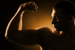 Strong arm. Handsome guy demonstrating his strong arm with biceps stock photo
