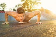 Handsome guy doing push-ups outdoors on a sunny summer day. Handsome young Caucasian guy doing push-ups outdoors on a sunny summer day stock images