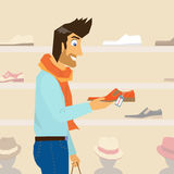 Handsome guy is doing shopping. Handsome guy interested in a new fashion shoes Stock Images