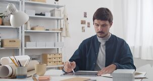 Handsome guy drawing on tablet and creating picture while sitting at his cosy workplace.Young man graphic illustrator