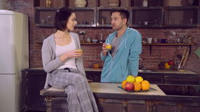 Handsome guy dressed in blue hoodie looking on girlfriend with love in flat. Couple in love drinking orange juice in the morning at home. Happy man talking with stock video footage