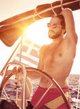 Handsome guy driving sailboat Royalty Free Stock Image
