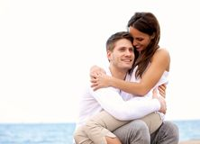 Handsome Guy Enjoying His Girlfriend. Portrait of a handsome guy enjoying the beach together with his girlfriend who is sitting on his lap royalty free stock photos