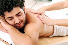 Handsome guy enjoying massage therapy. Young and handsome guy enjoying massage therapy Stock Photos