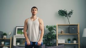 Handsome guy exercising with dumb-bells at home lifting weight training muscles. Handsome guy sportsman is exercising with dumb-bells at home lifting weight stock footage