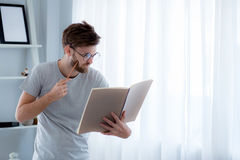 Handsome guy in eyeglasses is reading book preparing exam. With standing at the living room, education concept Stock Images