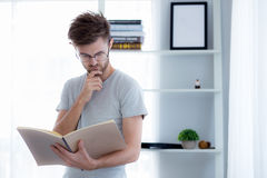 Handsome guy in eyeglasses is reading book preparing exam. With standing at the living room, education concept Stock Photography