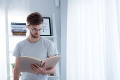Handsome guy in eyeglasses is reading book preparing exam with standing at the living room. Education concept Royalty Free Stock Image