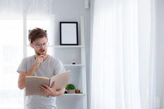 Handsome guy in eyeglasses is reading book preparing exam. And thinking with standing at the living room - education concept Royalty Free Stock Images