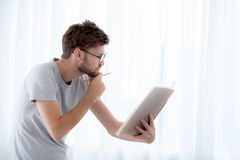 Handsome guy in eyeglasses is reading book preparing exam and thinking with standing at the living room. Education concept Royalty Free Stock Images