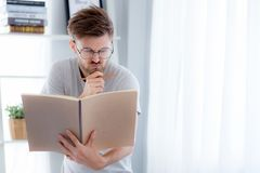 Handsome guy in eyeglasses is reading book preparing exam and thinking with standing at the living room. Education concept Royalty Free Stock Photography