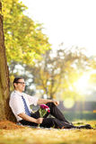 Handsome guy with flowers sitting on a grass and relaxing on a s Royalty Free Stock Images