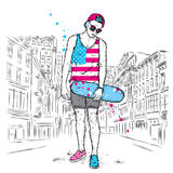 A handsome guy with glasses, a cap, shorts and a T-shirt. The skater. A boy with a skateboard. Teenager. Hipster on the city stree Stock Images