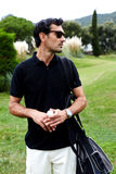Handsome guy with glasses on the golf course. Portrait of stylish golfer man in glasses standing on beautiful golf course looking away, handsome brunette hair royalty free stock photo
