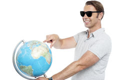 Handsome guy in goggles pointing at globe Royalty Free Stock Photos