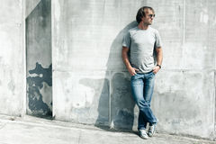 Handsome guy in gray t-shirt over street wall