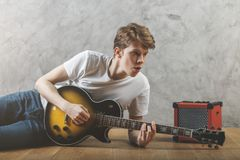 Handsome guy with guitar. Portrait of handsome guy lying on wooden floor with amplifier and guitar in hands. Concrete wall background. Music, concert, hobby Royalty Free Stock Images