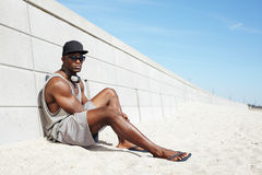 Handsome guy with headphones and sunglasses sitting on beach. Next to a wall. Muscular african american male model relaxing outdoors Royalty Free Stock Image