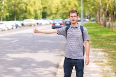 Handsome guy hitchhiking on the road. Handsome guy hitchhiking at the edge of the road Royalty Free Stock Photography